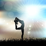 Silhouette of a female in a yoga pose in sunny landscape