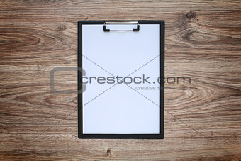 Blank white paper sheet A4 on clipboard. Wooden background.