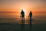 Silhouette of adult couple which costs in the sea and holds in hand footwear.