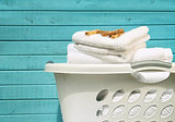 White laundry basket with towels and pins