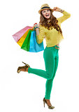 Cheerful woman in hat and bright clothes with shopping bags