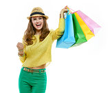 Woman in hat and bright clothes with shopping bags rejoicing