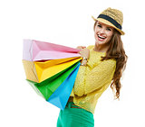 Woman in hat and bright clothes holding heavy shopping bags