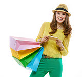 Woman in hat with shopping bags writing sms on smartphone