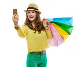 Woman in hat and bright clothes with shopping bags taking selfie