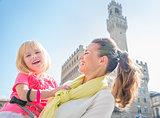 Portrait of smiling mother and daughter near Palazzo Vecchio
