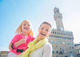 Portrait of happy mother and child near Palazzo Vecchio