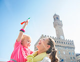 Happy mother and daughter with Italian flag near Palazzo Vecchio