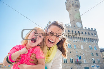 Portrait of cheerful mother and child near Palazzo Vecchio