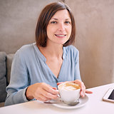 woman smiling at camera with coffee in her hands