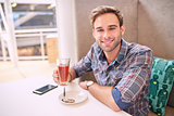 Good looking man looks straight at camera sitting in cafe