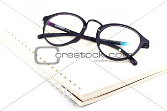 Blank spiral notebook and eyeglasses isolated on white backgroun
