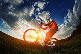 biker in orange jersey riding on green summer field