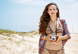 Bohemian woman with retro photo camera on white beach