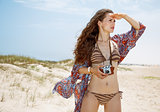 Bohemian woman with retro photo camera on beach looking aside