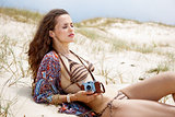 Relaxed bohemian woman with retro photo camera laying on beach