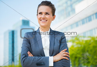 Smiling business woman in office district looking into distance