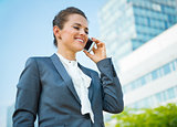 Smiling business woman in office district talking mobile phone