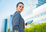 Portrait of business woman with tablet PC in office district