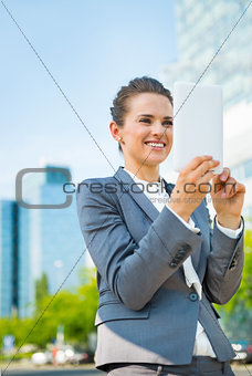 Smiling business woman using tablet PC in modern office district