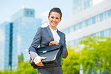 Smiling business woman in office district holding briefcase