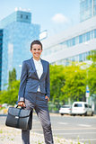 Happy business woman with briefcase in modern office district