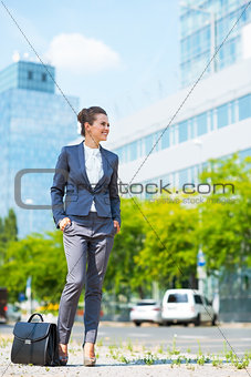 Business woman with briefcase standing in modern office district