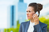 Business woman in modern office district talking smartphone