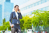 Happy business woman in modern office district talking cellphone
