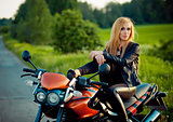 Outdoor fashion portrait of young sexy tan blonde woman posing  red scooter bike at sunshine.