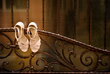 White wedding shoes hang a wrought iron fence