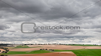 Green cultivated fields against cloudy stormy sky