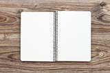 Mockup of open notepad with blank pages on wooden background.