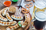 Grilled sausages with pretzels and mugs of beer