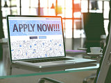 Apply Now on Laptop in Modern Workplace Background.