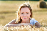 Portrait of a young woman who leans on a bale of hay