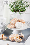 Sweet cookies on white tray with cups of coffee with green and w