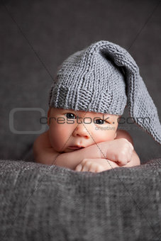 Beautiful newborn wearing a cute grey hat