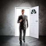 Businessman comes inside through door