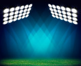 Green soccer field, illuminated spotlights