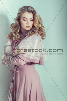 Portrait of beautiful blonde woman with curly hairstyle. Studio shoot.