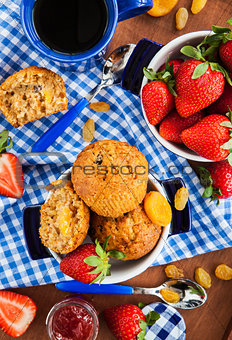 Breakfast with muffins, jam, coffee and strawberry