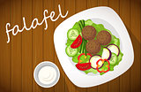 Plate of falafel with tzatziki sauce on wooden table. Top view.