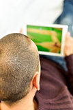 young man watching a baseball game in his tablet