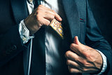 Money in pocket, businessman putting euro banknotes in suit pock
