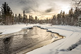 Snow-covered riverbank under the sunset sky. Northern Karelia. Russia.