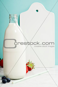 A bottle of milk, berries, white ceramic serving board and paper