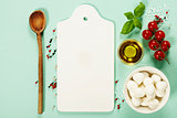 White ceramic serving board and salad ingredients over light blu