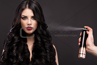 Beautiful brunette model: curls, classic makeup and red lips with a bottle of hair products. The beauty face.