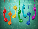 Telehone receivers of different colors hanging on the green back